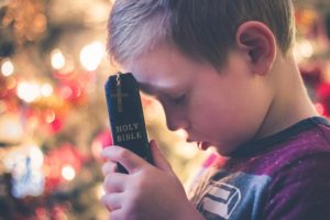 Small boy holding a bible