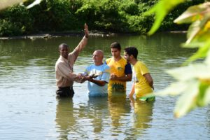 Black man baptizing three others