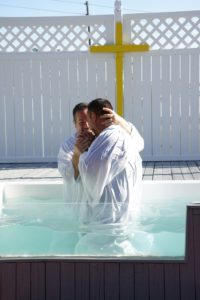 A man baptizing another man
